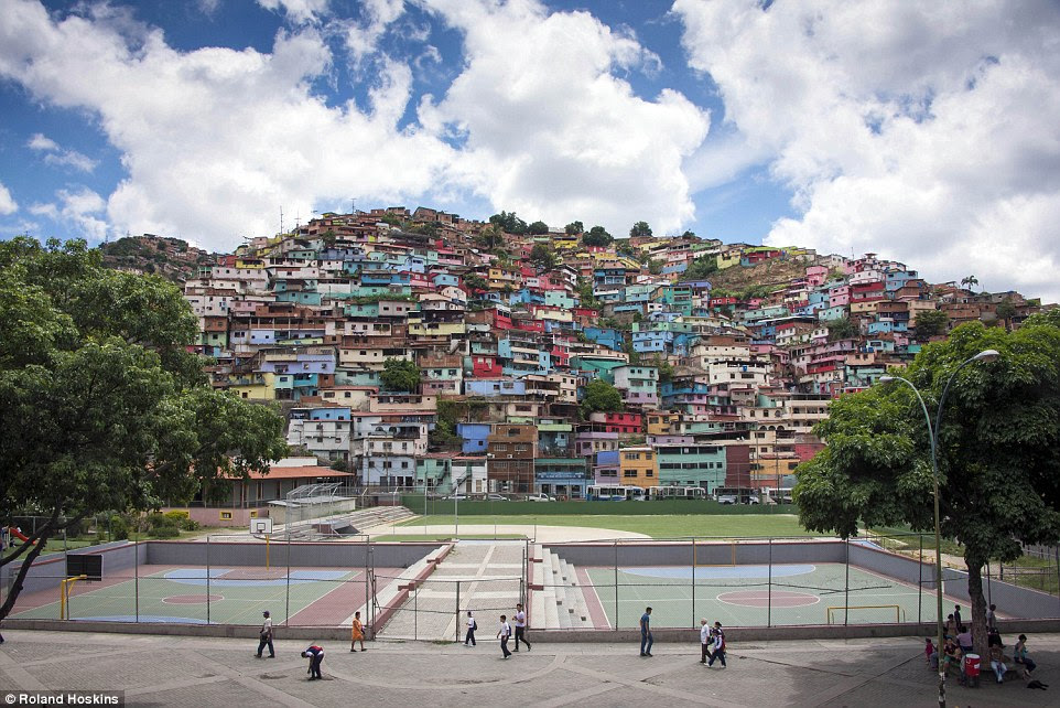 Underworld: Crime is intertwined with ordinary life in Caracas, where danger lurks just beneath the surface. As MailOnline interviewed the gang boss while being held at gunpoint, people were going about their business in the brightly-painted slum