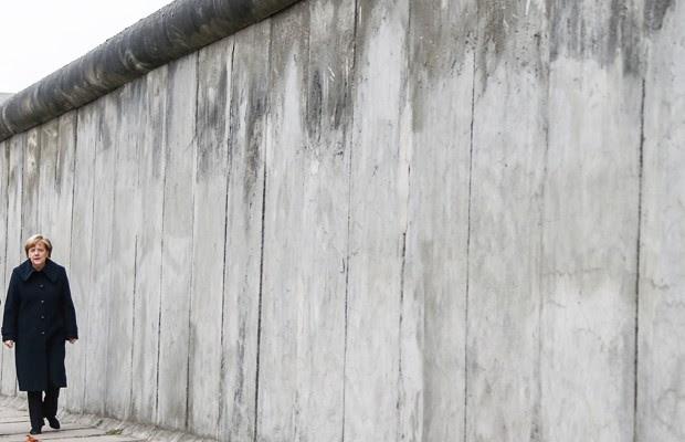 Chanceler Angela Merkel caminha ao lado de pedaço do antigo Muro de Berlim, em cerimônia que celebra neste domingo (9) da queda da barreira5 anos (Foto: Hannibal Hanschke/Reuters)