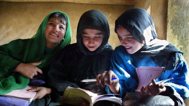 Tres adolescentes sonríen mientras miran sus libros en un colegio en Afganistán