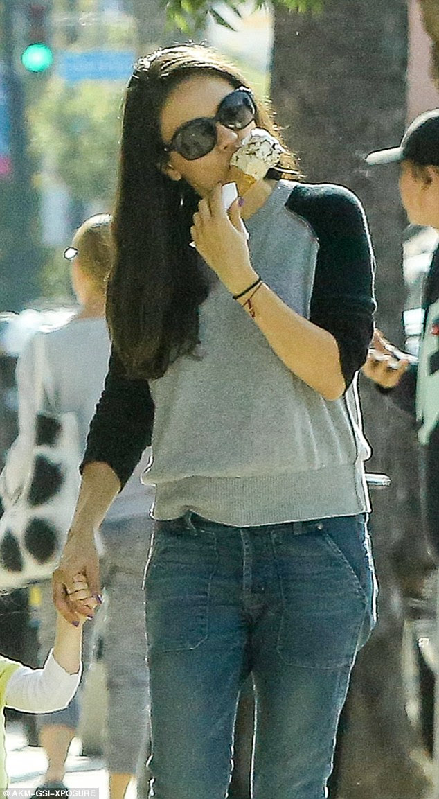 Slim physique: Mila licked on her cone as she strolled, dressed in Fidelity Denim skinny jeans and a black and gray long-sleeved sweater