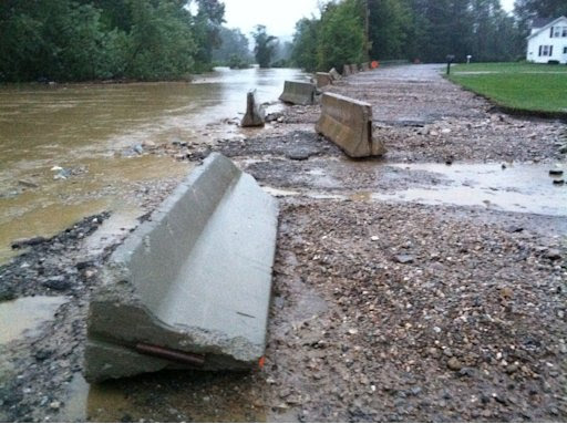 In this photo provided by Sarah Jones, Jersey barriers strewn along the historic Silk Road after flood waters from Tropical Storm Irene flooded the Walloomsac River in Bennington Vt., Sunday, Aug. 28, 2011. The flooding of the Walloomsac River was responsible for damage to at least one house and the loss of a car in Woodford, Vt. (AP Photo/Sarah Jones)