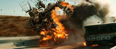 Bonecrusher obliterates a bus on a freeway as he pursues the Autobots in TRANSFORMERS.