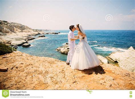 Elegant Smiling Bride And Groom Walking On The Beach