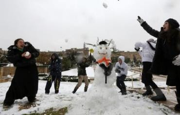 Girls have a snowball fight in Jerusalem, December 12, 2013.