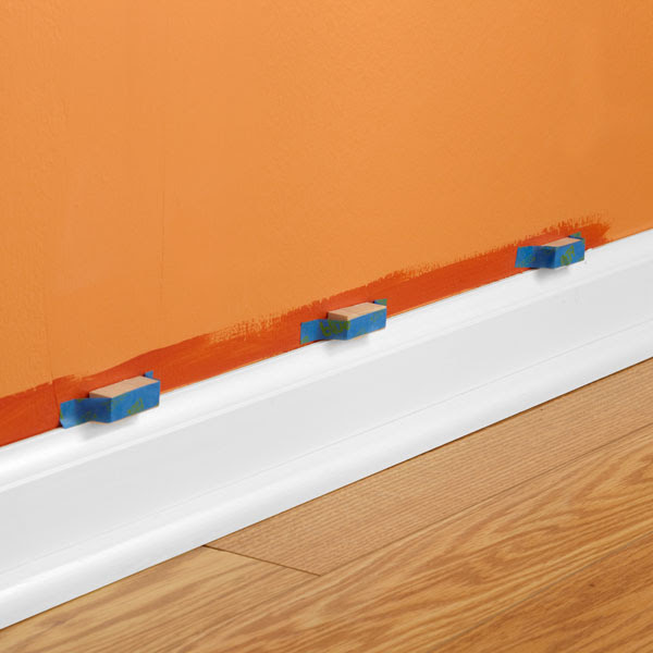 Pure white baseboard with bright orange wall paint wood planks floors