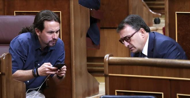El líder de Podemos, Pablo Iglesias, y el portavoz del PNV, Aitor Esteban, conversan durante un pleno celebrado en el Congreso de los Diputados. EFE/Zipi