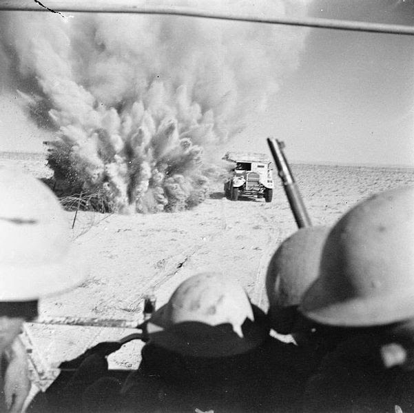 File:A mine explodes close to a British truck as it carries infantry through enemy minefields and wire to the new front lines.jpg