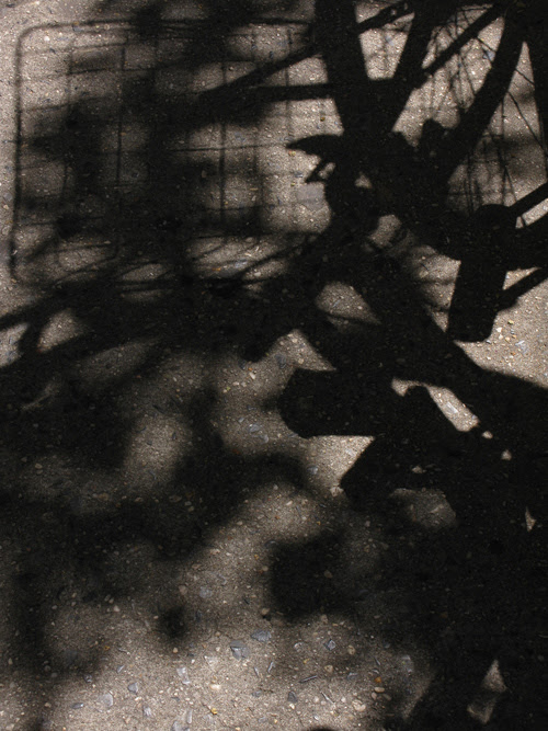 shadow of a bicycle and its basket on a Manhattan sidewalk, NYC