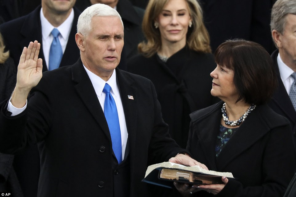 Vice President Mike Pence is sworn in as this wife Karen holds the bible during the 58th Presidential Inauguration at the U.S. Capitol in Washington, Friday, Jan. 20, 2017