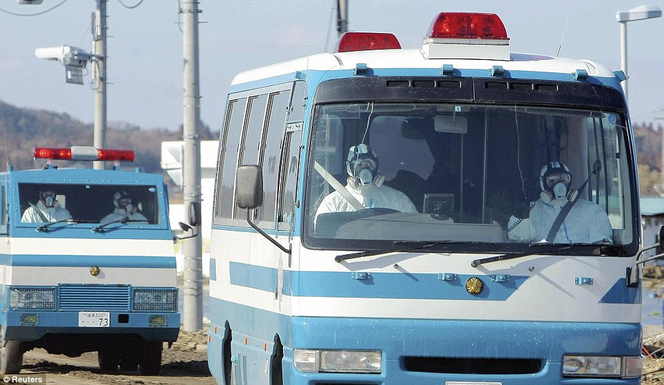 Taking no chances: Police wearing protective clothing and respirators head towards the nuclear plant in Minamisouma City, Fukushima Prefecture yesterday