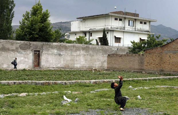 Menino brinca com bola em frente à casa que abrigou o ex-líder da rede al-Qaeda Osama bin Laden, em Abbottabad, no Paquistão. As forças paquistanesas informaram que começaram neste sábado (25) a demolição da casa onde o terrorista foi morto pelos american (Foto: Reuters)