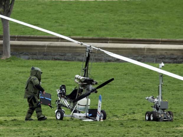 Membro do esquadrão antibombas analisa girocoptero que pousou nesta quarta-feira (15) no jardim do Capitólio, em Washington, Estados Unidos (Foto: AP Photo/Manuel Balce Ceneta)