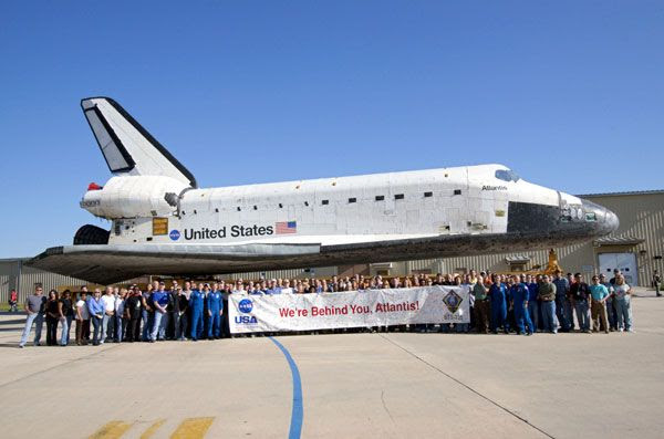 Kennedy Space Center workers take a group photo with space shuttle Atlantis during her rollover to the VAB, on May 17, 2011.