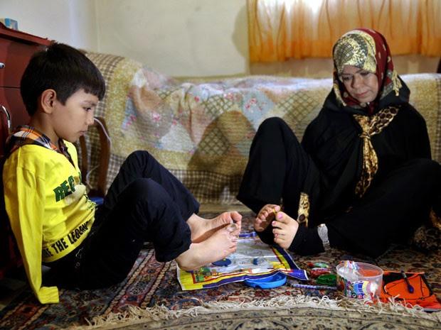 Roohollah Jafar, de 9 anos, tem aulas de pintura com a professora aposentada (Foto: Ebrahim Noroozi/AP)