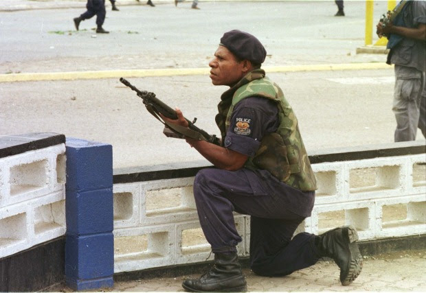 Democratic challenges: a riot policeman outside Murray Army Barracks in Port Moresby.