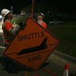 Traffic Management Inc. workers install a shuttle crossing sign on Lincoln Boulevard outside Los Angeles International Airport, as roads are closed to move space shuttle Endeavour