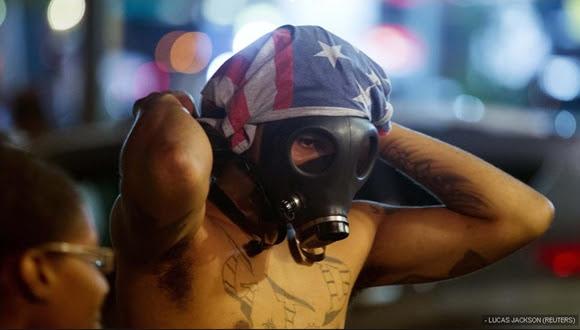 Un manifestante con la cara cubierta por una máscara de gas durante los disturbios que se saldaron con 31 detenidos.