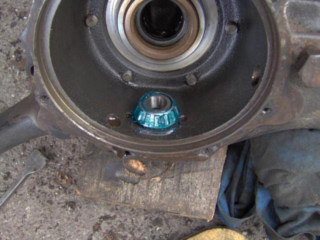 Feed the housing back over the driveshaft and hook the lower bearing into