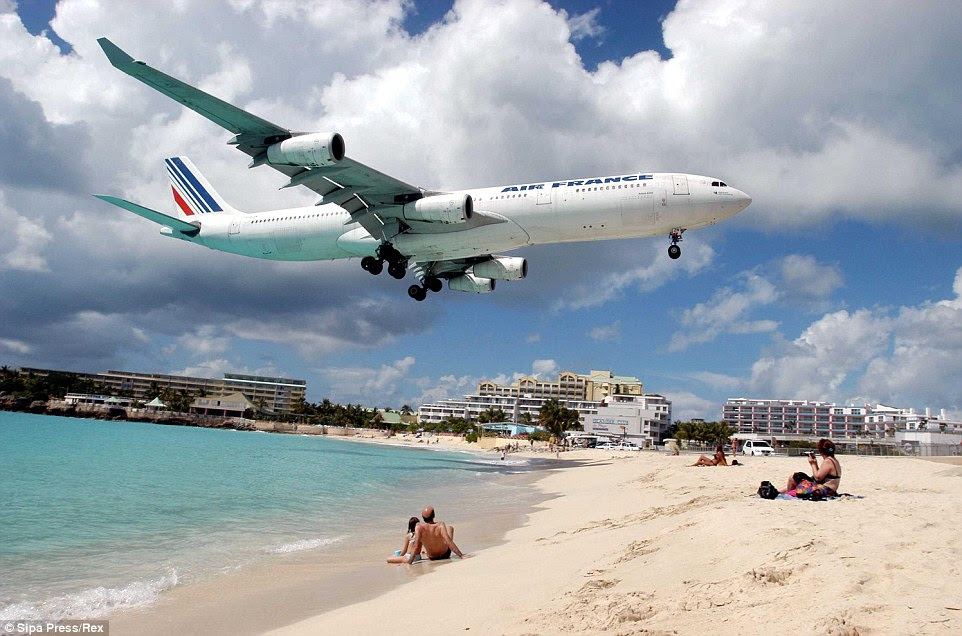 Look out below! You're not seeing things - airliners zoom over holidaymakers' heads on Maho Beach as they land on Saint Martin Island in the Caribbean