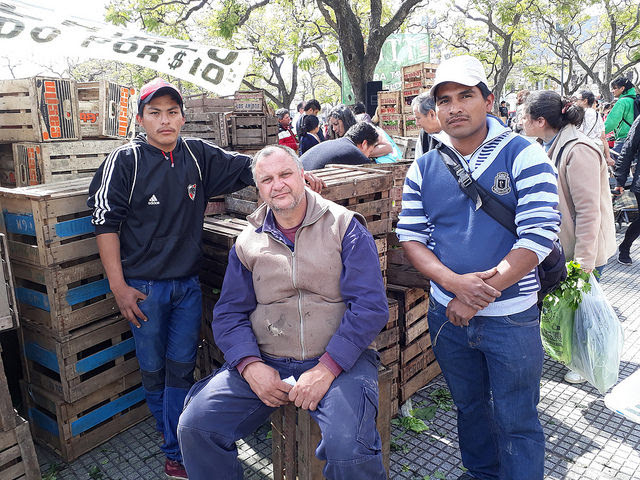 Roberto Eizaguirre, Guillermo Riquelme and Mario Garcia (left to right), farmers from the rural area of La Plata, Argentina, during the fair that small farmers set up in a central square in Buenos Aires to sell their vegetables directly to consumers at prices much lower than those seen in stores. Credit: Daniel Gutman/IPS