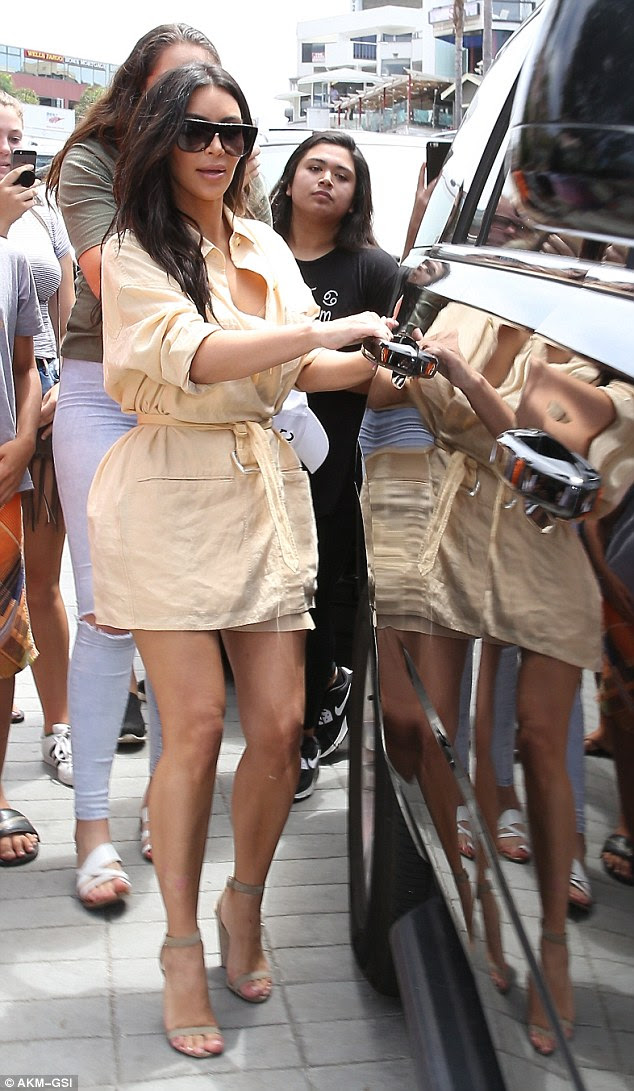 Popular: The stunner was mobbed by fans as she made her way from her hotel to a waiting SUV that reflected hertoned legs in its shiny exterior