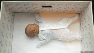 Bebé durmiendo en una caja