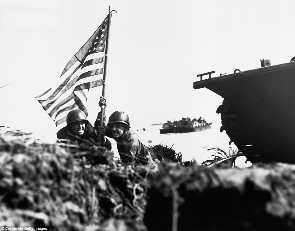 Pictured:Two US soldiers plant an American flag attached to a boat hook on the beach at Guam, just eight minutes after U.S. Marines and Army assault troops landed on the Central Pacific island on July 20, 1944. The Americans lost more than 1,700 men in the fight to reclaim the island and the Japanese lost over 18,000