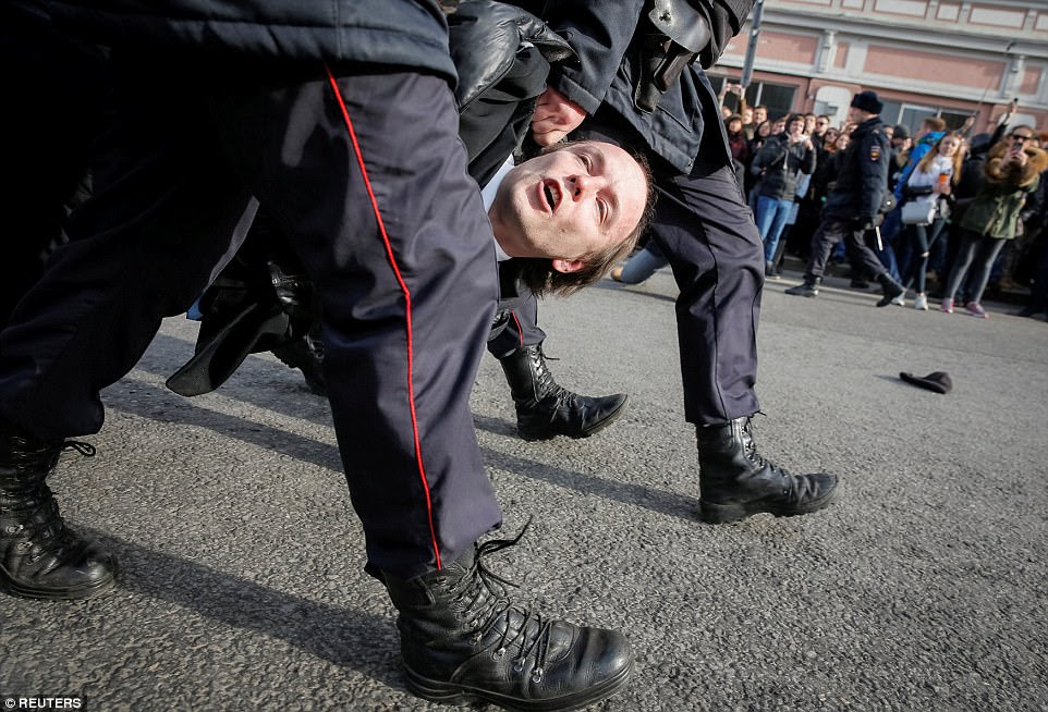Russian police detain an opposition supporter during a rally in Moscow on March 26, when about 60,000 people participated in anti-corruption protests across 80 towns and cities across the country. Hundreds of demonstrators were detained, including opposition leader Alexei Navalny and Anti-Corruption Foundation employees