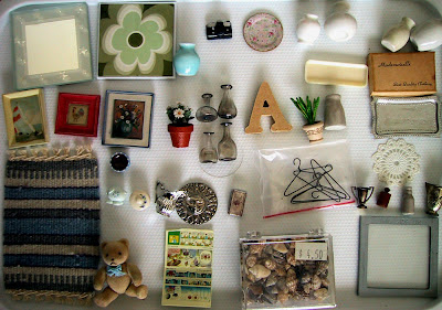 A selection of modern dolls' house miniature accessories, arranged neatly.