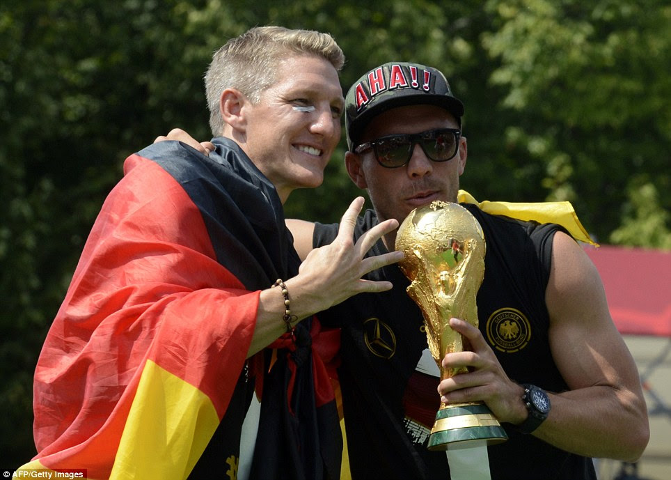 Pleased: Bastian Schweinsteiger and Lukas Podolski pose with the World Cup trophy in Berlin