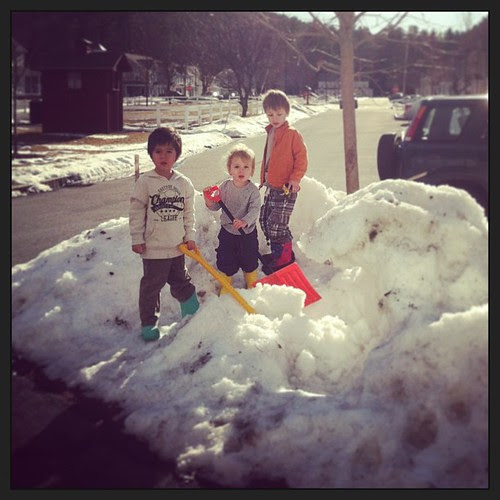 "Three little dudes ""mining"" their hill of melting snow."