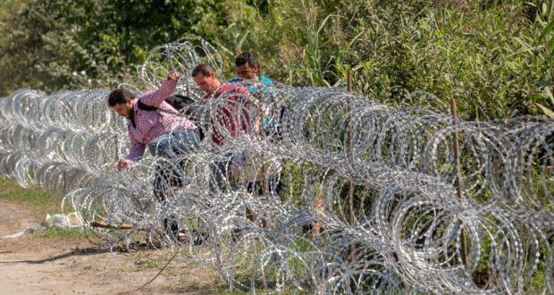 Migrants jump through the border fence from Serbia into Hungary. Critics see the  fence as a costly publicity stunt. Photograph: Matt Cardy/Getty Images