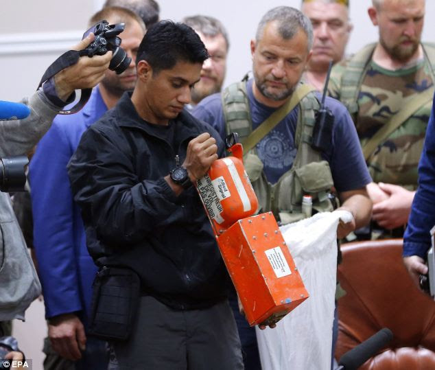 A Malaysian expert checks one of the two black boxes. The small handing over ceremony has finally solved the question as to what had happened to the two vital devices