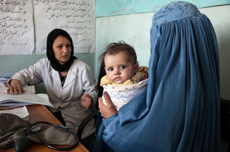 Una mujer afgana visita el centro médico local con su hijo de cinco meses.