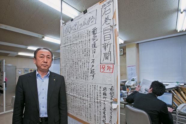 """HEROÍSMO Koichi Omi, diretor de um jornal de Ishinomaki, ao lado da versão escrita à mão no dia do terremoto – não havia energia nem internet. A manchete diz """"O fogo se espalha""""  (Foto: Hitoshi Katanoda)"""