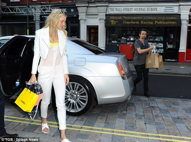 He's got some serious baggage! The rocker, 37, assumed chivalry duties as they arrived at the Marylebone diner, carrying her Christian Louboutin shopping bags