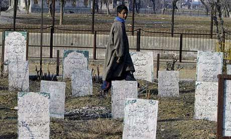 A Kashmiri boy walks in a graveyard in Srinagar, India