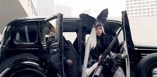 De blanco, todo lo que ahora cambia a negro.  Gaga lleva alas de pájaro en la cabeza.  En la antigua Grecia y otras civilizaciones, los cuervos se consideraban presagios de muerte.
