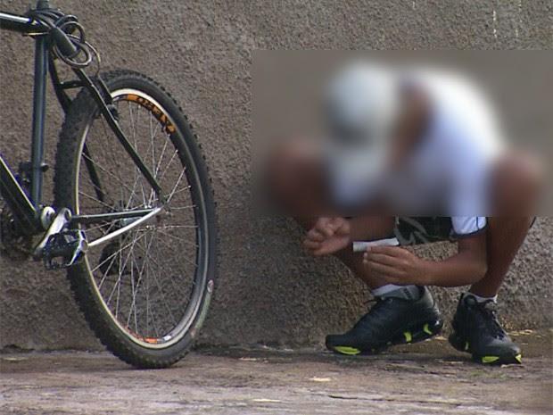 Menor recolhe maconha do chão enquanto prepara cigarro da droga em frente à escola em Ribeirão Preto (Foto: Reprodução/EPTV)