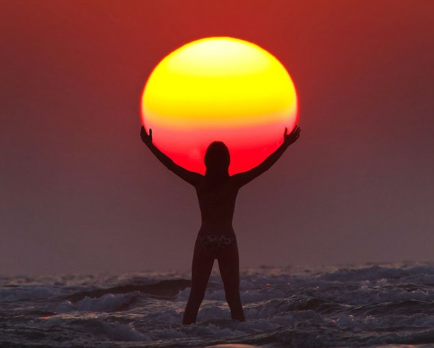 Whole new ball game: A woman appears to be holding up the sun in one of a series of stunning images captured by an amateur photographer in Saudi Arabia