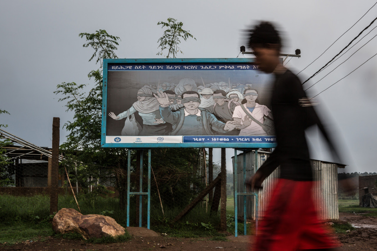 A billboard set up by Ethiopian authorities in Adi-Harush camp for Eritreans who have fled their country warned about human smugglers, saying, 'Illegal movement is like walking blindfolded. Let's stay alert.' The refugees, who want to get to Europe, aren't deterred.