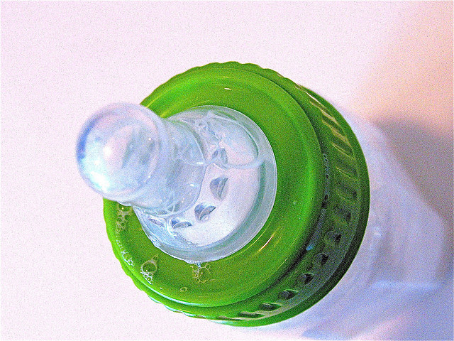plastic baby bottle with green ring