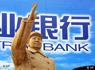 ** TO GO WITH THE STORY SLUGGED CHINA THE GREAT PARADOX ** A statue of communist founder Mao Zedong stands in front of a bank billboard in Zhengzhou in central China, Oct. 17, 2002. As it convenes a congress that is expected to install a new generation of leaders, the ruling Communist Party is trying to transform itself in order to stay relevant amid economic and social reforms that it unleashed. (AP Photo/Greg Baker)