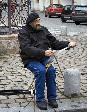 A busker playing the musical saw in Prague, Cz...