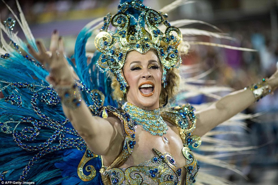 A woman wearing peacock-style plumage and a bright gold, blue and green bikini costume appeals to the 70,000-strong crowd