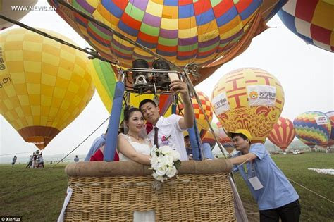Chinese couples marry in a group ceremony held in hot air