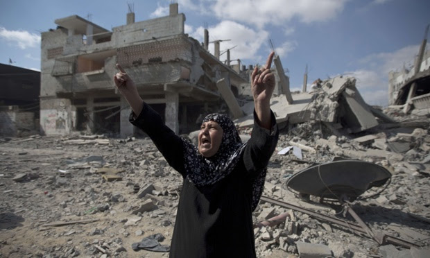 A Palestinian woman looks at the rubble of destroyed buildings in the Shejaiya district of Gaza City.