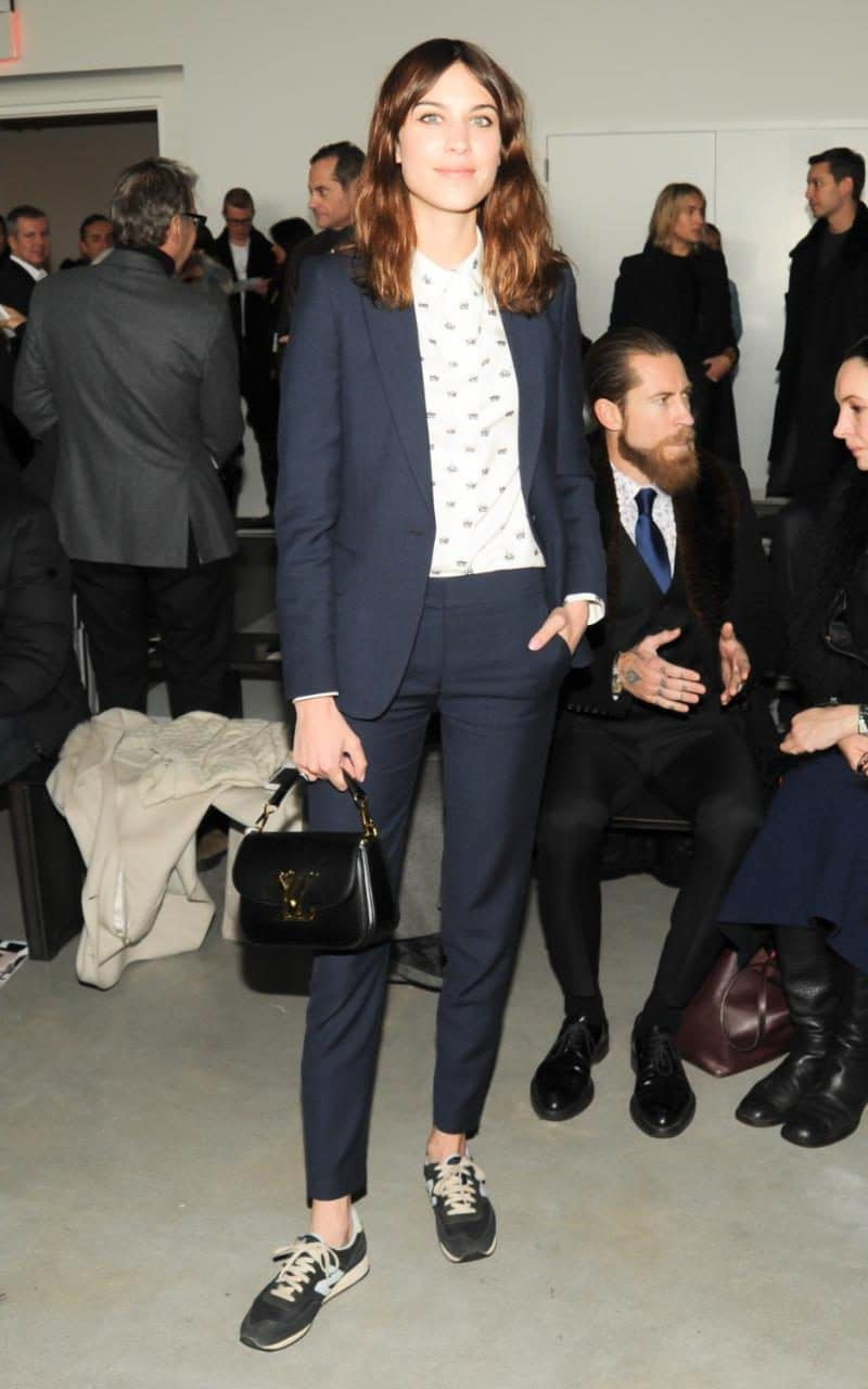 At New York Fashion Week Alexa Chung dressed down her navy ankle-skimming trouser suit with New Balance trainers and a printed shirt