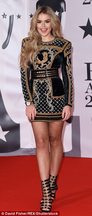Bold:Singer Tallia Storm, 17, looked lovely in a sharply-cut little black dress, covered in a delicate glitzy embellishment all over in silvers and golds, hinting that it was a Balmain design