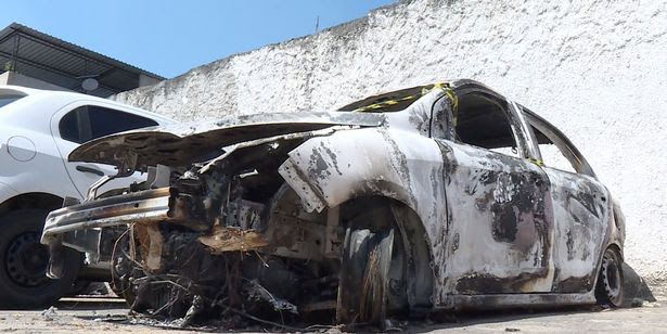 A man looks at the burned-out rental car of missing Greek ambassador to Brazil Kyriakos Amiridis, at a parking lot outside the police station in Belford Roxo, in the Brazilian state of Rio de Janeiro, on December 30, 2016, a day after it was found with a body inside.